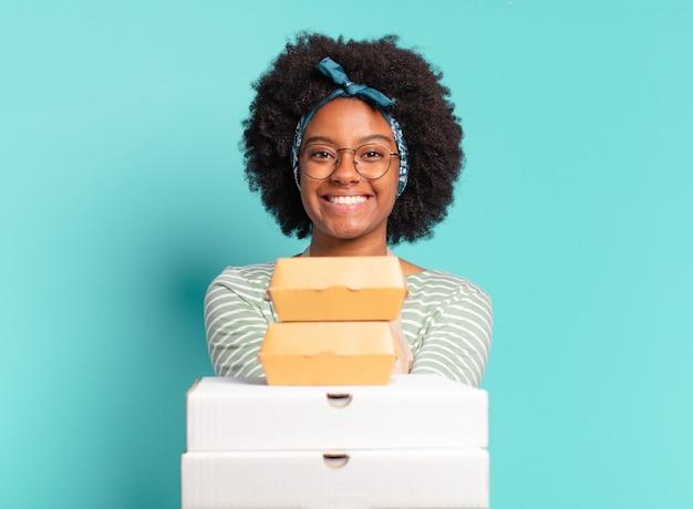 Jeune jolie femme afro livrer avec des boîtes de pizza et hamburgers à emporter