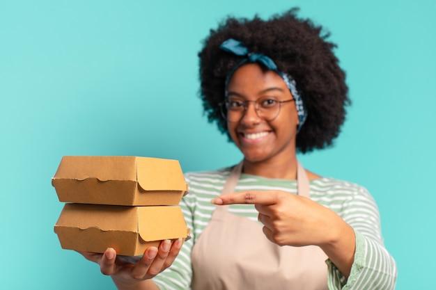 Jeune jolie femme afro livreuse avec des boîtes de hamburger à emporter