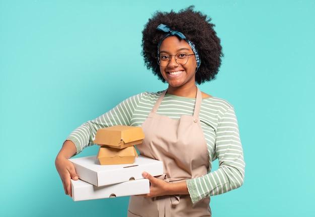 Jeune jolie femme afro livreuse avec des boîtes de pizza et de hamburgers à emporter
