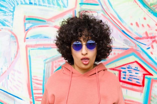 Jeune jolie femme afro, perplexe et confuse, avec une expression stupide et stupéfaite regardant quelque chose d'inattendu contre le mur de graffitis