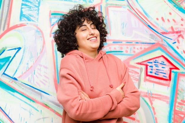 Jeune jolie femme afro qui rit joyeusement, les bras croisés, avec une pose détendue, positive et satisfaite contre le mur de graffitis
