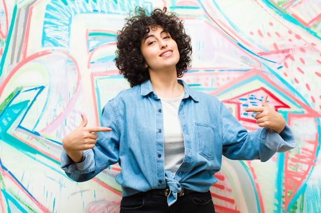 Jeune jolie femme afro à la recherche de fierté, arrogante, heureuse, surprise et satisfaite, se montrant soi-même, se sentir gagnante contre un mur de graffitis
