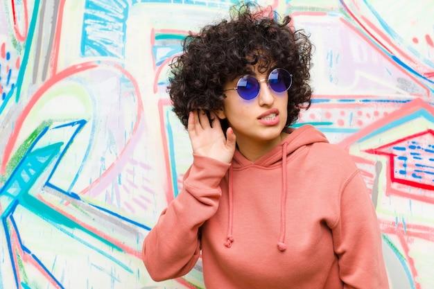 Jeune jolie femme afro à la recherche sérieuse et curieuse, à l'écoute, tentant d'entendre une conversation secrète ou des commérages, espionnant contre un mur de graffitis