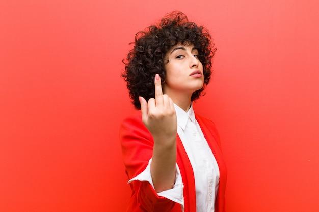Jeune jolie femme afro se sentant en colère, agacée, rebelle et agressive, renversant le majeur, se battant