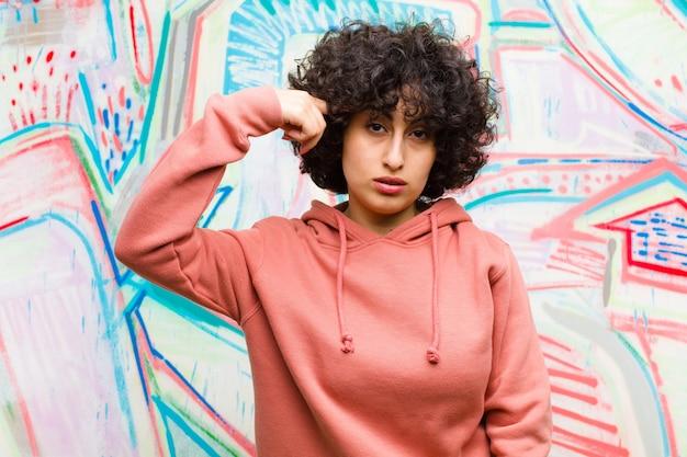 Jeune jolie femme afro se sentant confuse et perplexe, montrant que vous êtes folle, folle ou déchaînée contre un mur de graffitis