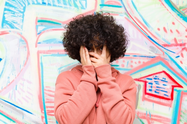 Jeune jolie femme afro se sentant effrayée ou embarrassée, jetant un coup d'œil ou espionnant, les yeux à demi couverts de mains contre le mur de graffitis