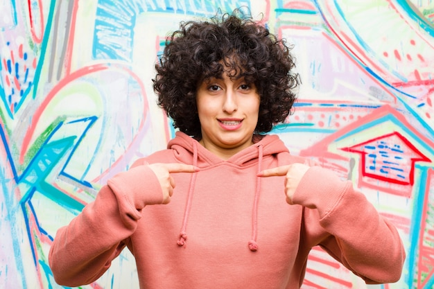 Jeune jolie femme afro se sentant heureuse, surprise et fière, se pointant sur elle-même avec un regard excité et émerveillé contre le mur de graffitis