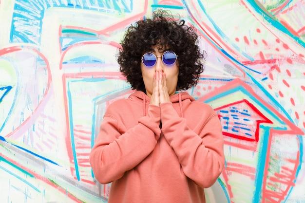 Jeune jolie femme afro se sentant inquiète, bouleversée et effrayée, se couvrant la bouche avec les mains, semblant inquiète et s'être ruinée contre un mur de graffitis