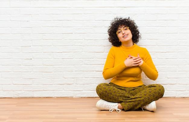 Jeune jolie femme afro se sentant romantique, heureuse et amoureuse, souriant joyeusement et se tenant la main près du cœur assis sur le sol