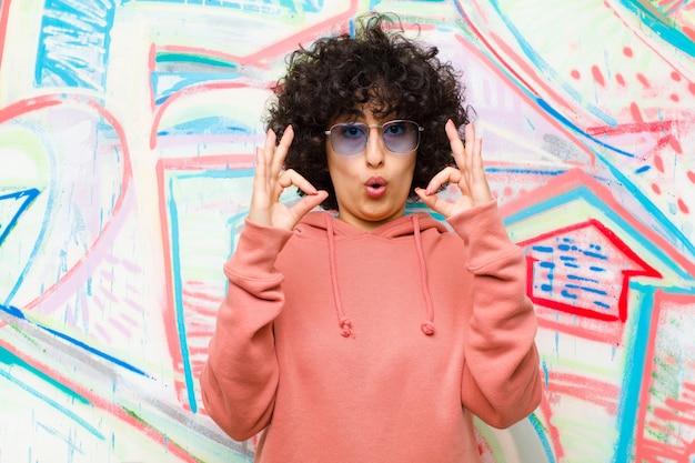 Jeune jolie femme afro se sentir choquée, émerveillée et surprise, montrant son approbation en faisant signe avec le mur de graffitis à deux mains