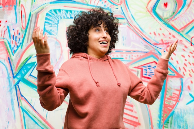 Jeune jolie femme afro se sentir heureuse, émerveillée, chanceuse et surprise, célébrant la victoire avec ses deux mains en l'air contre le mur de graffitis