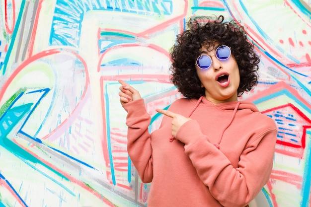 Jeune jolie femme afro se sentir joyeuse et surprise, souriant avec une expression choquée et en montrant le mur de graffitis