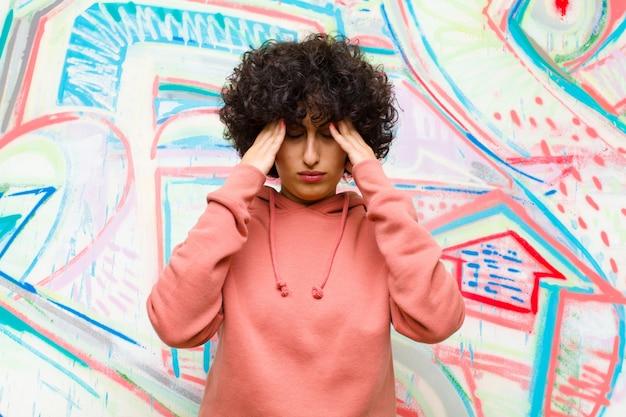Jeune jolie femme afro semblant stressée et frustrée, travaillant sous pression avec mal à la tête et troublée par des problèmes contre le mur de graffitis