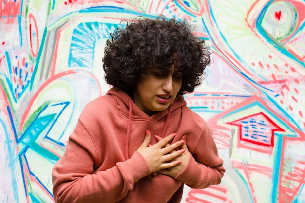 Jeune jolie femme afro semblant triste, blessée et navrée, tenant ses deux mains près du cœur, pleurant et se sentant déprimée contre un mur de graffitis