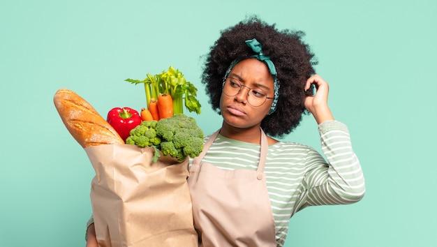 Jeune jolie femme afro souriant joyeusement et rêvassant ou doutant, regardant sur le côté et tenant un sac de légumes
