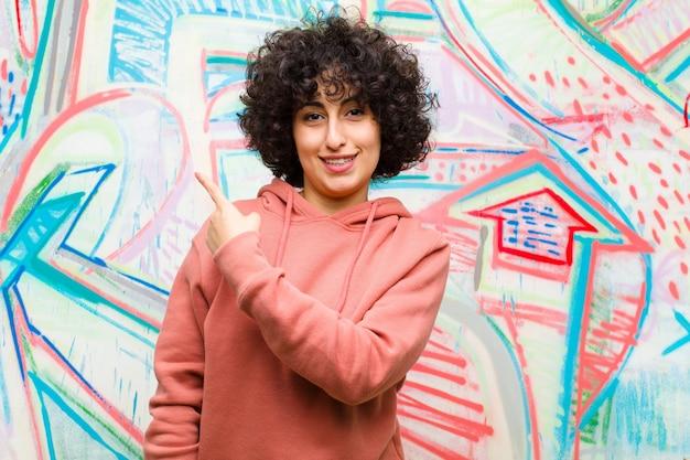 Jeune jolie femme afro souriante gaie, se sentant heureuse et pointant vers le côté et vers le haut, montrant un objet dans l'espace de la copie contre le mur de graffitis