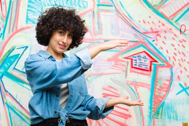 Jeune jolie femme afro souriante, heureuse, positive et satisfaite, tenant ou montrant un objet ou un concept sur l'espace copie contre le mur de graffitis