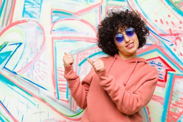 Jeune jolie femme afro souriante, pointant vers le fond sur le côté, se sentant heureuse et satisfaite du graffiti
