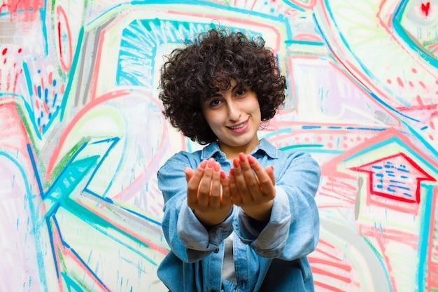 Jeune jolie femme afro souriante avec un regard amical, confiant et positif, offrant et montrant un objet ou un concept contre un mur de graffitis