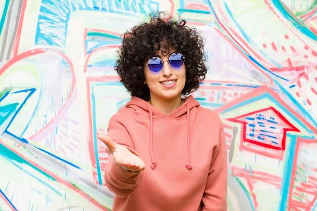 Jeune jolie femme afro souriante, semblant heureuse, confiante et amicale, offrant une poignée de main pour conclure un marché, coopérant contre le graffiti