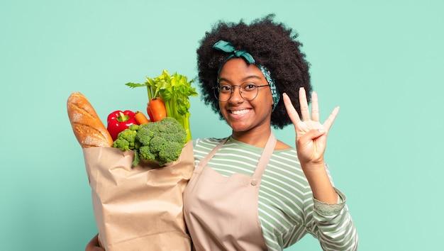 Jeune jolie femme afro souriante et à la sympathique, montrant le numéro trois ou troisième avec la main en avant, compte à rebours et tenant un sac de légumes