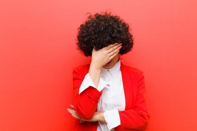 Jeune jolie femme afro stressée, honteuse ou contrariée, avec un mal de tête couvrant le visage avec la main