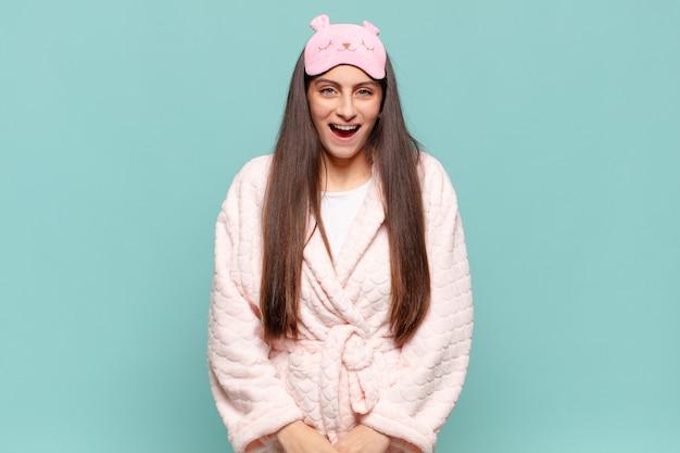 Jeune jolie femme à l'air heureuse et agréablement surprise, excitée par une expression fascinée et choquée. concept de réveil en pyjama