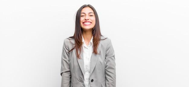 Jeune jolie femme à l'air heureux et maladroit avec un large sourire amusant et loufoque et des yeux grands ouverts, isolés contre un mur blanc