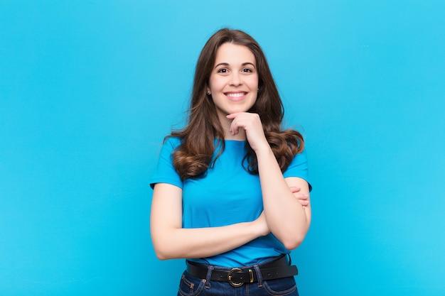 Jeune jolie femme l'air heureux et souriant avec la main sur le menton, se demandant ou posant une question, en comparant les options contre le mur bleu