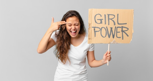 Jeune jolie femme à l'air malheureuse et stressée, geste de suicide faisant un signe d'arme à feu et tenant une bannière de pouvoir de fille