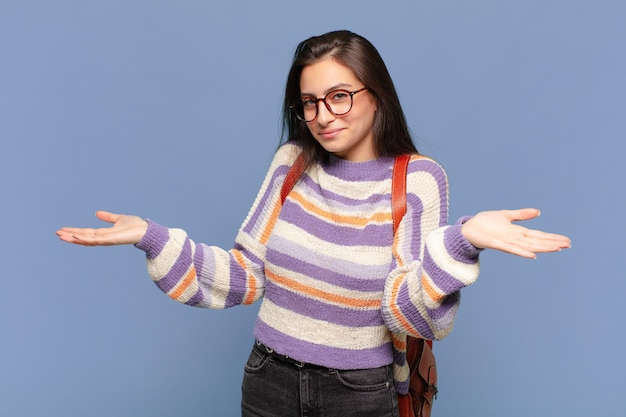 Jeune jolie femme à l'air perplexe, confuse et stressée, se demandant entre différentes options, se sentant incertaine