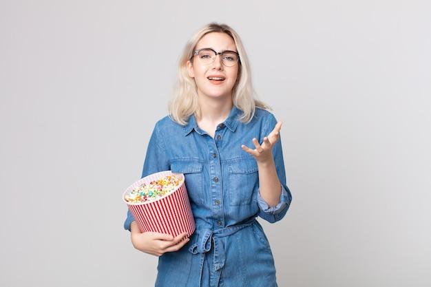 Jeune jolie femme albinos à la recherche désespérée, frustrée et stressée avec un seau de pop corns