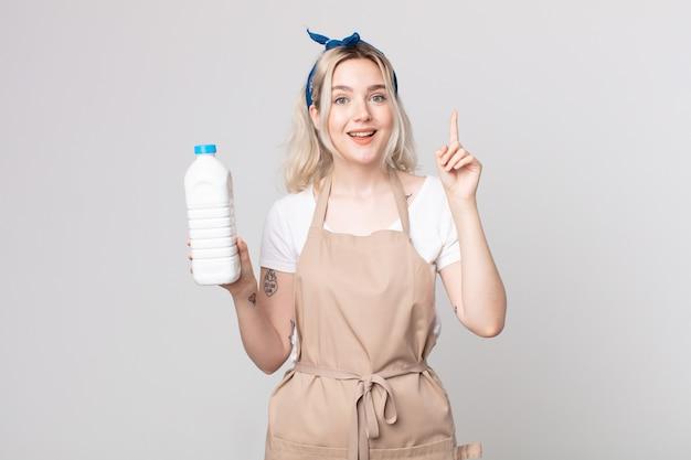 Jeune jolie femme albinos se sentant comme un génie heureux et excité après avoir réalisé une idée avec une bouteille de lait