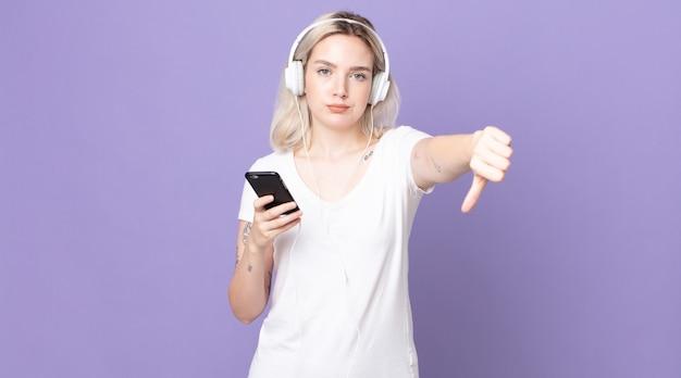 Jeune jolie femme albinos se sentant croisée, montrant les pouces vers le bas avec des écouteurs et un smartphone