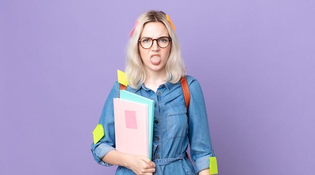 Jeune jolie femme albinos se sentant dégoûtée et irritée et tirant la langue. concept d'étudiant