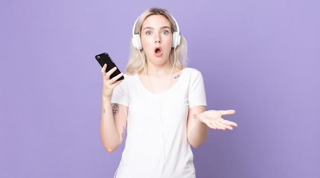 Jeune jolie femme albinos se sentant extrêmement choquée et surprise avec des écouteurs et un smartphone
