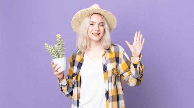 Jeune jolie femme albinos souriant joyeusement, agitant la main, vous accueillant et vous saluant et tenant un cactus de plante d'intérieur