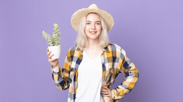 Jeune jolie femme albinos souriant joyeusement avec une main sur la hanche et confiante et tenant un cactus de plante d'intérieur