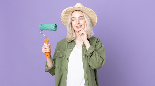 Jeune jolie femme albinos souriant joyeusement et rêvant ou doutant et tenant un rouleau de peinture