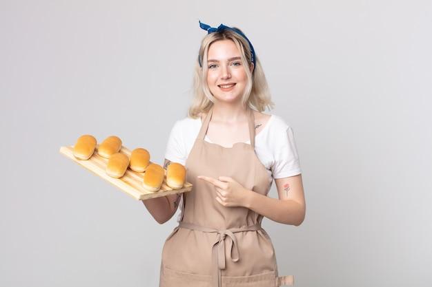 Jeune jolie femme albinos souriant joyeusement, se sentant heureuse et pointant vers le côté avec un plateau de petits pains