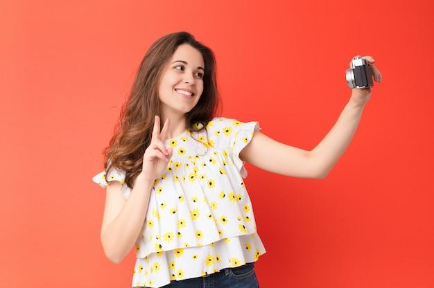 Jeune jolie femme avec un appareil photo vintage contre le mur rouge
