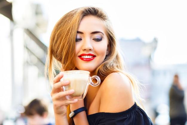Jeune jolie femme appréciant, boire une tasse de cappuccino, latte, café au café de rue du matin.