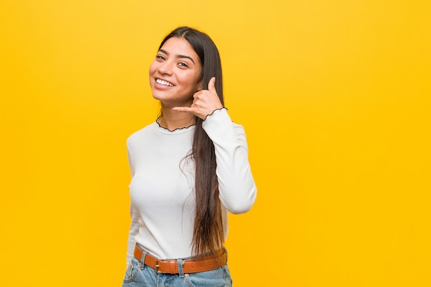 Jeune jolie femme arabe contre un jaune montrant un geste d'appel avec les doigts.