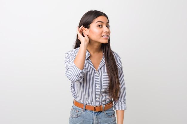 Jeune jolie femme arabe essayant d'écouter un commérage.