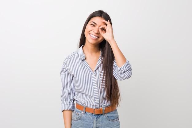Jeune jolie femme arabe excitée, gardant le geste correct pour les yeux.