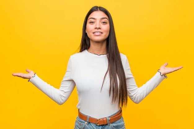 Jeune jolie femme arabe fait échelle avec les bras, se sent heureuse et confiante.
