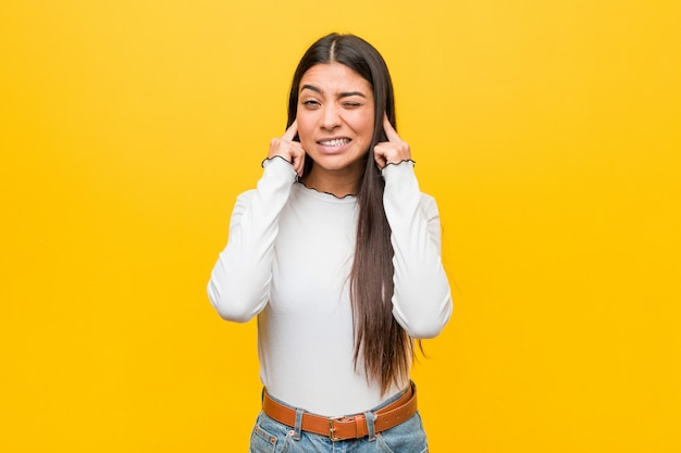 Jeune jolie femme arabe sur un fond jaune couvrant les oreilles avec les mains.