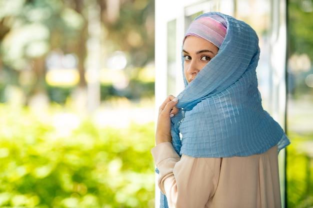 Jeune jolie femme arabe en hijab vous regarde par-dessus son épaule dans un environnement naturel