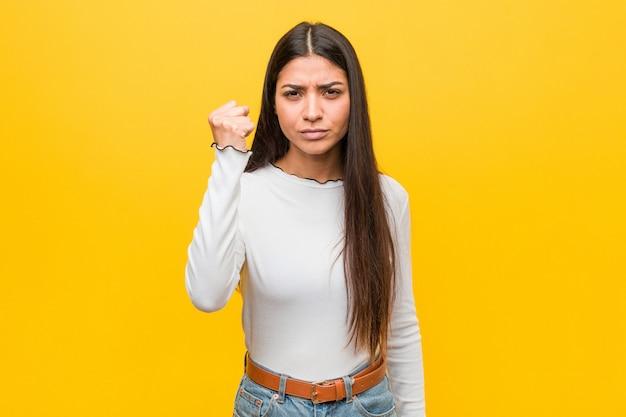 Jeune jolie femme arabe montrant le poing à la caméra, expression faciale agressive.