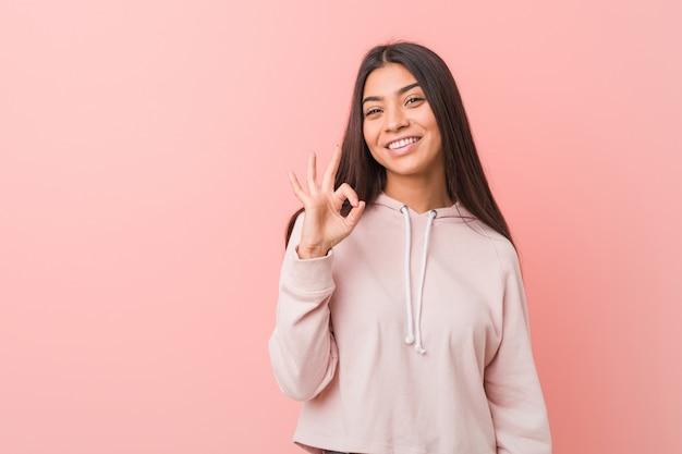 Jeune jolie femme arabe portant un look sport décontracté cligne de l'oeil et tient un geste correct avec la main.
